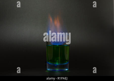 Burning absinthe in a glass on a black background 2018 - Stock Photo