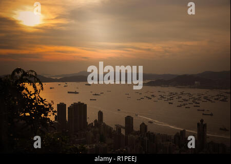 Sunset over Hong Kong harbour from Lugard Lookout, Victoria Peak. Dazzling orange sun sets over distant islands with city highrises in the foreground. - Stock Photo