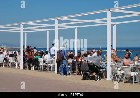 People sit in a beach bar at Barceloneta in Barcelona, Spain on April 17, 2018. - Stock Photo