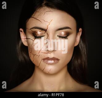 Woman with cracked face as cosmetic and dehydration effect concept. - Stock Photo