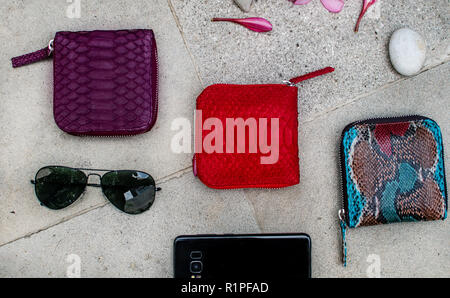 Exotic and luxury set of hand made leather wallet . Multi colored. Leather craft. On a stone tile with background with Plumeria . Python snake fashionable handbag, purse, clutch. Python accessories - Stock Photo