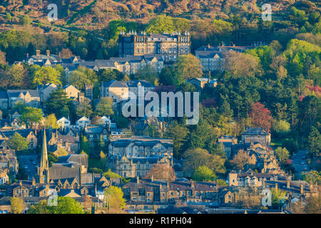 Sunny evening view over buildings (mainly residential) nestling in Wharfe Valley under moorland - Ilkley town centre, West Yorkshire, England, UK. - Stock Photo