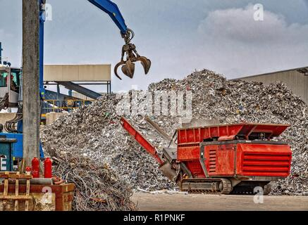 A grab crane lifting large amounts of scrap metal into a machine which reduces the sixe of the waste metal for further recycling processes. - Stock Photo