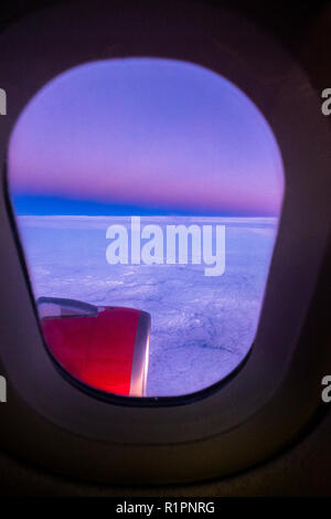 Airplane window looking out over the wing and engine on an Iberia Express flight with the sunrise lighting up the clouds. - Stock Photo
