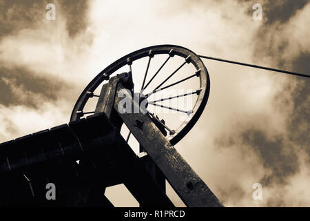 Old Victorian coal shaft tower and wheel pulley with colour toning - Stock Photo