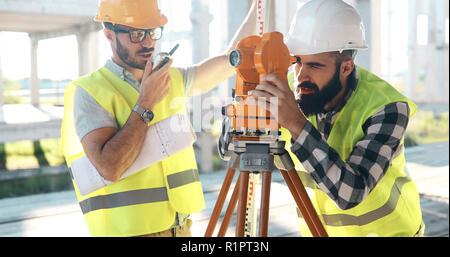 Team of architects people in group on construciton site check documents - Stock Photo