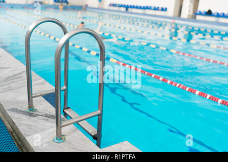 Swimming pool handrails. Clear blue water on background. - Stock Photo