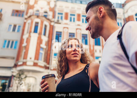 Mixed race couple in love walking in city. Arab man and white woman drinking coffee, talking and chilling outdoors - Stock Photo