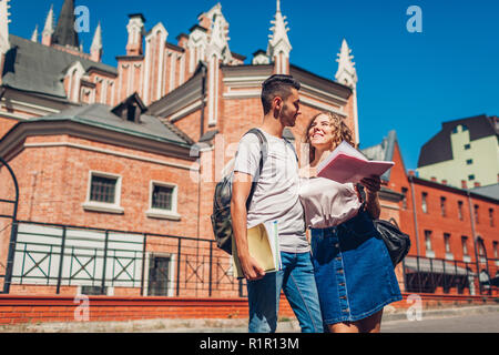 Mixed race couple of college students walking by university with copybooks. Young arab man and white woman studying outdoors - Stock Photo