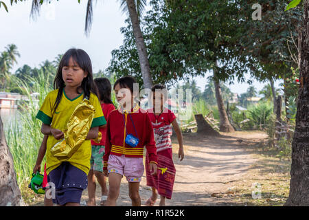 Don Det, Laos - April 22, 2018: Young girls walking through a path next to the Mekong river between two villages on the 4000 islands - Stock Photo