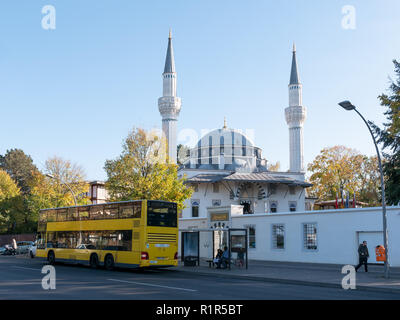 BERLIN, GERMANY - OCTOBER 21, 2018: Yellow BVG Bus In Front of Sehitlik Mosque In Berlin, Germany - Stock Photo