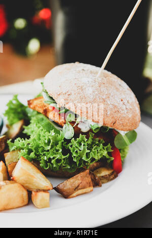 Vegan burger with lettuce, tomatoe, fried potatoes and garlic dill sauce on white plate at vegetarian restaurant - Stock Photo
