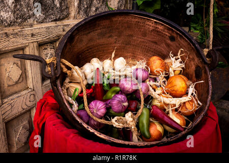 old copper casserole with garlic, onions and peppers on a red cloth in an old dark kitchen - Stock Photo