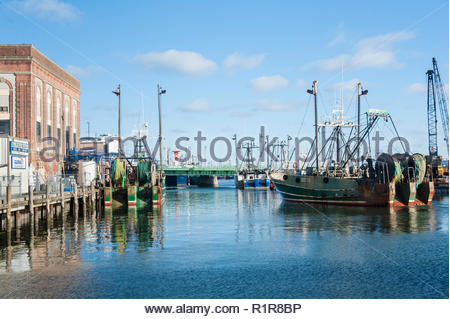 New Bedford, Massachusetts, USA - March 15, 2017: Fishing vessel easing toward dock on New Bedford waterfront - Stock Photo