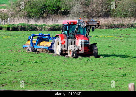 Nice new red tractor towing a very heavy grass roller stranded deeply in the middle of a very muddy field and sinking. - Stock Photo