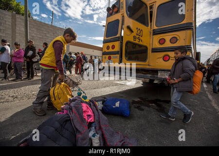 Tijuana, Mexico. 13th Nov, 2018. Orlando (l) and Isaac Cruz take their backpacks and a pram after arriving in the Mexican city of Tijuana with a new group of migrants. There they will have breakfast at a meeting point. The group rode a bus for three days. Credit: Omar Martinez/dpa/Alamy Live News - Stock Photo