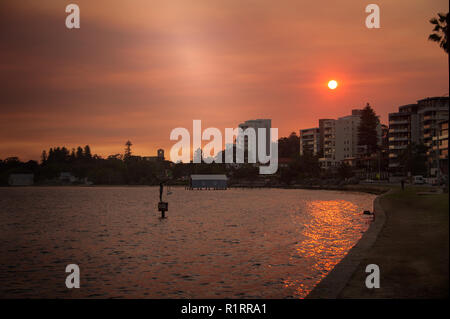Sunset over Matilda Bay, Perth, Australia. Colourful sky with orange sun casts glow over the River Swan - Stock Photo