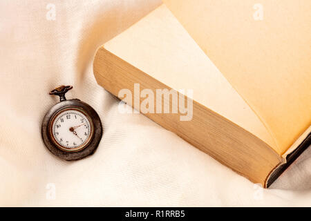 Page Turner Concept. A watch showing early morning hours and a finished book on a pillow. Impossible to put down the book - Stock Photo