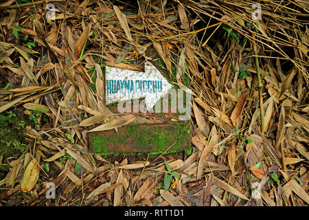 Signpost on the ground for hiking route of HUAYNAPICCHU MOUNTAIN in the archaeological site of Machu Picchu, Cusco Region, Peru - Stock Photo