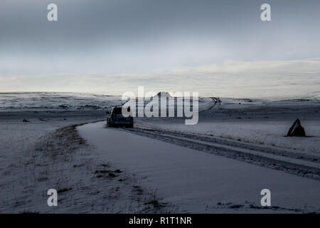 Dirt road / jeep track with a jeep silhouette in the snowy highlands, Iceland - Stock Photo