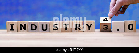 Hand is turning a dice and changes the word 'Industry 3.0' to 'Industry 4.0' - Stock Photo