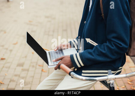 cropped view of african american teleworker using laptop while leaning on bicycle - Stock Photo