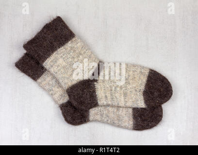 male grey knitted socks made of dog hair  on grey background close up, top view - Stock Photo
