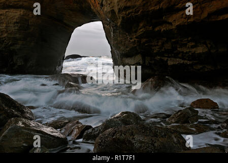 OR02384-00...OREGON - In-coming tide bring water back through the archway, into the Devil's Punchbowl; Devil's Punchbowl State National Area. - Stock Photo