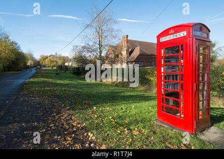 Old-fashioned red telephone box or kiosk on The Street near the village hall in the village of Rotherwick in Hampshire, UK, now used as a library - Stock Photo