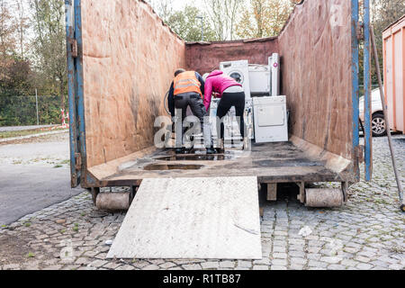 Woman and man giving electrical appliances to recycling center, a washing machine - Stock Photo