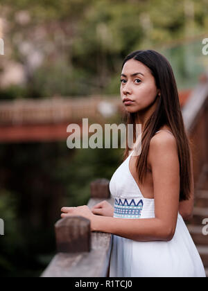 Beautiful brunette girl in white dress looking away at the park - Stock Photo