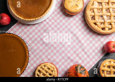 Directly above view of a table with a pink towel and various sweet pies, pumpkin pies, apple pies, and raspberry, with copy space in the middle. - Stock Photo