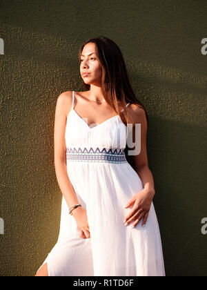 Beautiful brunette girl in white dress stand by green wall - Stock Photo