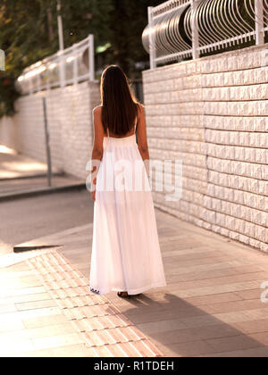 Beautiful brunette girl in white dress stand on the street - Stock Photo