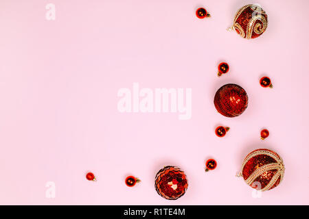 Red christmas balls are creating frame on pink pastel background. Place for text. Festive concept. - Stock Photo