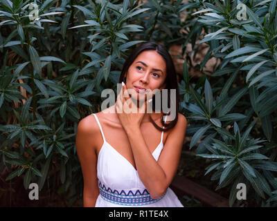 Beautiful brunette girl in white dress sits near by green tree - Stock Photo