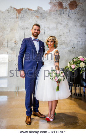 Newlywed couple pose right after their marriage ceremony - Stock Photo