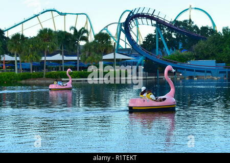Orlando, Florida. September 29, 2018. People enjoying flamingo boat  on lake with Rollercoaster background at Seaworld Marine Theme Park. - Stock Photo