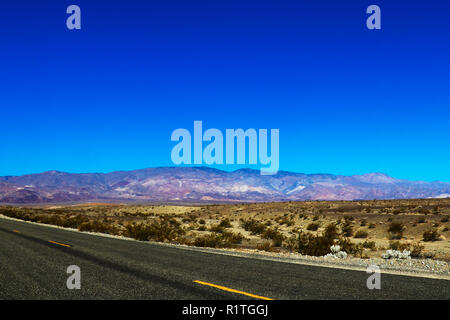 Classic vertical panorama view of an endless straight road running through the barren scenery of the American Southwest with extreme heat haze on a be - Stock Photo