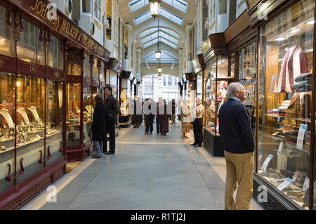Shoppers in the Burlington Arcade, a covered shopping arcade that runs behind Bond Street from Piccadilly to Burlington Gardens, London. - Stock Photo