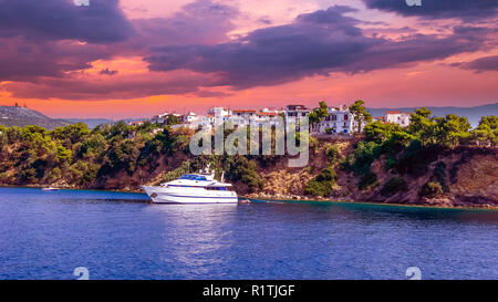 Sunset over Skiathos town, Greece. Luxury yacht in the bay of Skiathos, near the harbour - Stock Photo