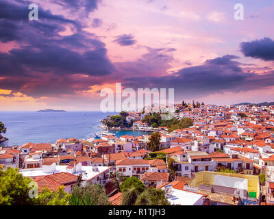 Sunset over Skiathos town on Skiathos Island, Greece. Beautiful view of the old town with boats in the harbor. - Stock Photo