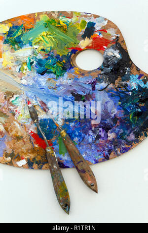 Vibrant multi-coloured artists oil or acrylic paints palette on textured white paper with palette knives