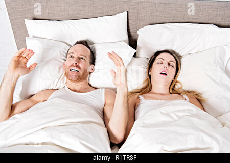 A Stressed men tired ears because snoring - Stock Photo