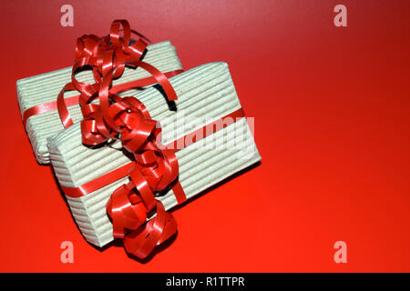 vintage xmas boxes background with copy space, top view of gift box wrapped in cardboard packaging with red ribbon on red surface - Stock Photo