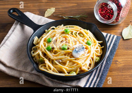 Food concept homemade spaghetti creamy white sauce in cast-iron skillet pan on wood background - Stock Photo