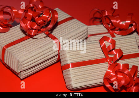 birthday or christmas present boxes, top view of gift box wrapped in cardboard packaging with red ribbon on red surface - Stock Photo