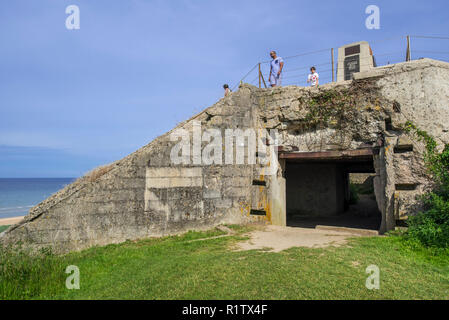 Tourists visiting the Fifth Engineer Special Brigade Memorial on top of German bunker at Omaha Beach, Colleville-sur-Mer, Calvados, Normandy, France - Stock Photo