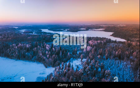 Aerial view of the winter snow covered forest and frozen lake from above captured with a drone in Lithuania. - Stock Photo