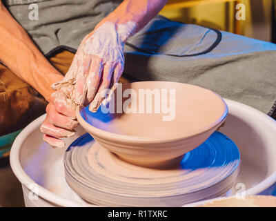 Creating earthenware and traditional pottery concept. Experienced male potter's hands creating beautiful clay product - bowl - using professional tool - Stock Photo